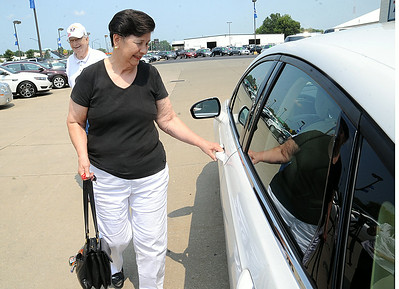 Nancy Mathewson, of Doylestown, formerly of Elyria, picks up the 2014 Ford Fusion she won with a ticket in the St. Jude Dream Home giveaway event at Nick Abraham Ford in Elyria on Aug. 7. STEVE MANHEIM/CHRONICLE