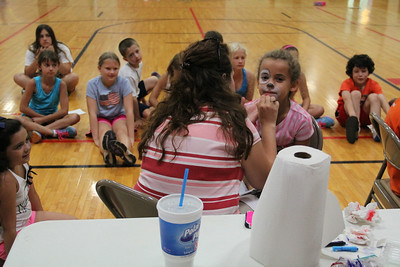 Alyce Williams, 9, of Elyria gets her face painted at East Recreational Center during a kid's day camp activity on Aug. 6.  ALEC SMITH   CHRONICLE