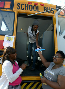 Makeisha Price, 16, and LaVonda Sims, 16, hand school supplies to Bre-Aja Tucker, 17, all of Lorain, to stuff the school bus outside of Credit Recovery Academy on Aug. 14.  KRISTIN BAUER | CHRONICLE
