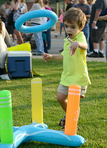 Liam Starett, 3, of Amherst plays with a ring toss set up at the annual dancing downtown event in Amherst on Aug. 2. KRISTIN BAUER   CHRONICLE