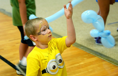 Anthony Reitz, 6, of Elyria, plays with his newly made balloon animal after having his face painted during a Reach and Rise Discovery Camp activity at East Recreation Center on Aug. 6.  KRISTIN BAUER | CHRONICLE