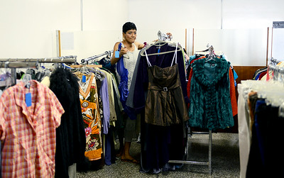 Gail Robinson, of Elyria, sorts through clothes at a soon-to-be open thrift shop in Elyria on Aug. 12. KRISTIN BAUER | CHRONICLE