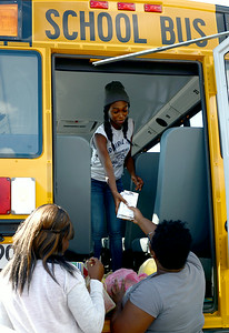 Makeisha Price, 16, and LaVonda Sims, 16, hand school supplies to Bre-Aja Tucker, 17, all of Lorain, to stuff the school bus outside of Credit Recovery Academy on Aug. 14.  KRISTIN BAUER   CHRONICLE