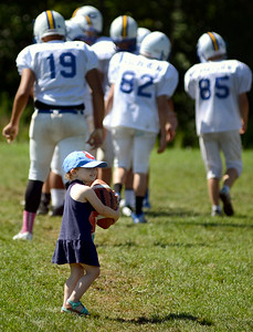 Olivia Gantz, 2, of Lorain, practices her ball-handling skills along with the Clearview High football team during practice on Aug. 13.  KRISTIN BAUER | CHRONICLE