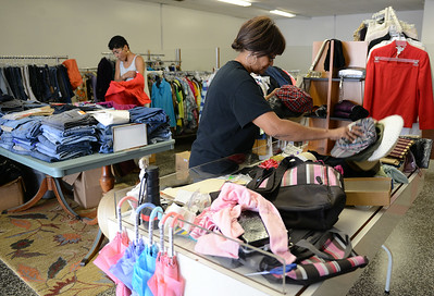 Gail Robinson and Rhonda Washington, both of Elyria, sort through clothes at a soon-to-be open thrift shop in Elyria on Aug. 12.  KRISTIN BAUER   CHRONICLE