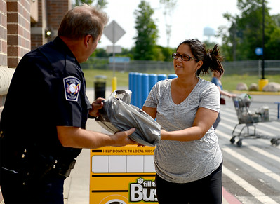 Johana Bierek, of Avon, and an Amherst teacher, hands a bag full of donated school supplies to school resource officer Pat Sullivan during the Fill the Bus event at Walmart in Avon on Aug. 8. KRISTIN BAUER   CHRONICLE