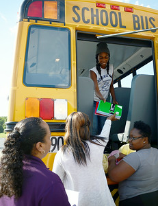 Lucy Acevedo, a parent volunteer, and Credit Recovery Academy students Makeisha Price, 16, and LaVonda Sims, 16, hand school supplies to Bre-Aja Tucker, 17, all of Lorain, to stuff the school bus outside of Credit Recovery Academy on Aug. 14.  KRISTIN BAUER | CHRONICLE