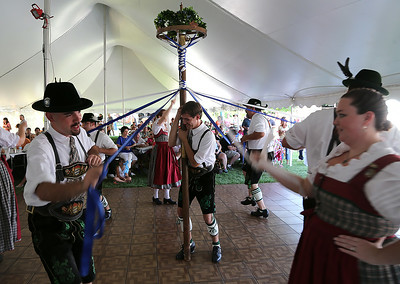 Brent Miller of Lorain holds up the maypole for his fellow STV Bavaria dancing group at the German Heritage Festival at the Sandstone Historical Center in Amherst on Aug. 9. BRUCE BISHOP/CHRONICLE