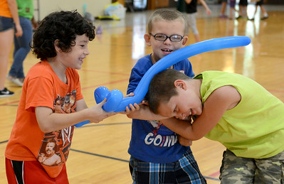 Riley Hawkins, 8, Phillip Lilly, 8, and Cody Turvey, 8, all of Elyria, play with their inflatable balloon swords on Aug. 6.  KRISTIN BAUER   CHRONICLE