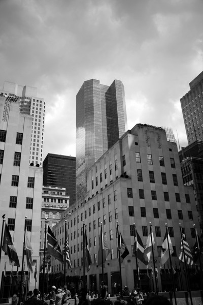 The Rockefeller Plaza flags and nearby building seen from ground level in front of the 30 Rock building in New York City.