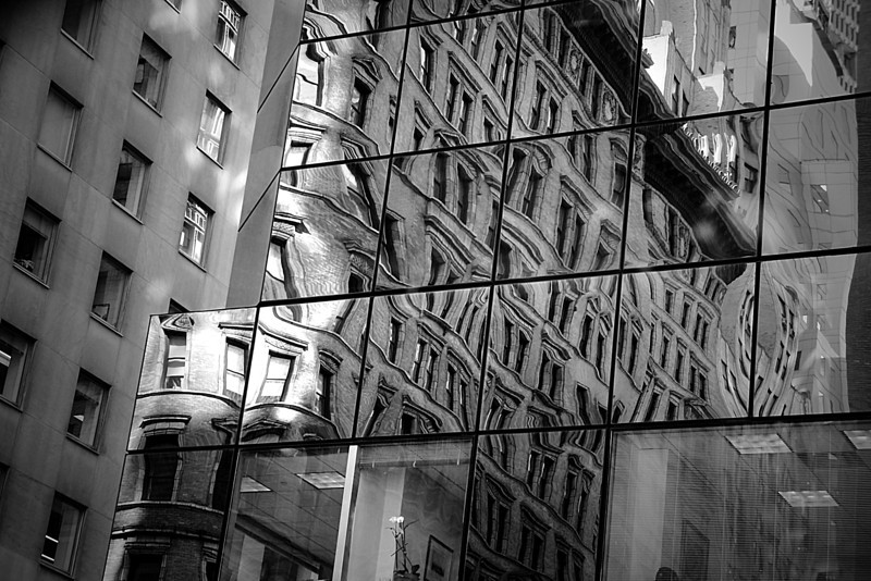 Distorted reflections in a building in New York City in monochrome.