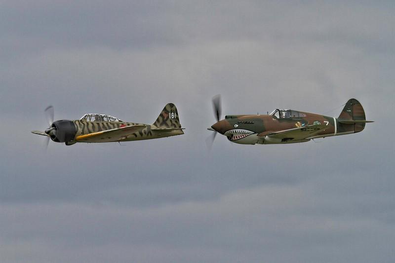 "A Mitsubishi A6M3-22 Reisen (""Zero"") and a Curtiss P-40C Tomahawk in friendly flight.<br /> Photo © Carl Clark"