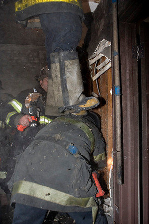 "Squad 5 fireman Pat Noonan giving fellow Squad fireman Tom Garswick a lift into the attic during the search for hidden fire known as ""overhaul""."
