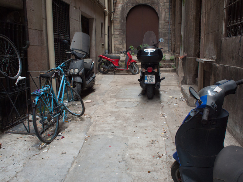 A courtyard behind gates, love the different propelled scooters/motorbikes and the push bike and spare wheel.