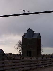 Barn in Idaho with arrow sign above farm entrance.