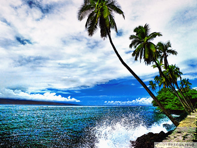 """Lahaina Ocean Spray"" ~ Waves crash on a seawall in Lahaina on Maui as overhanging coconut palms reach for the sky as the island of Lanai appears in the distance."
