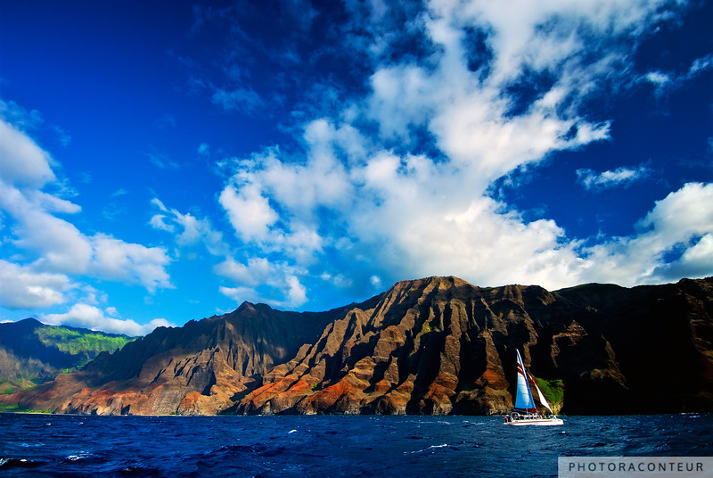 """Nā Pali Coast of Kauai"" ~ Sailboat navigates the majestic Nā Pali Coast of Kauai between Kalalau Valley and Alapi'i Point amongst mountains that rise 4000 feet above the Pacific Ocean."