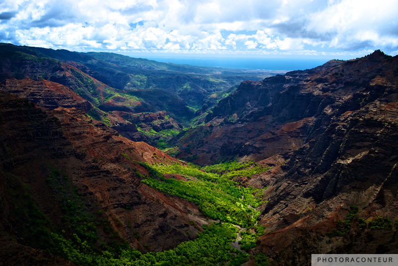 """Waimea Canyon Ocean Vista"" ~ The crystal blue waters of the Pacific Ocean appear beyond the rugged walls and lush green Waimea Canyon on Kauai."