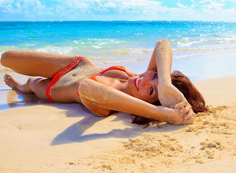 Shauna in an orange bikini lying on the sand at lanikai beach.  ©Tomás del Amo 2009