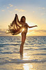 beautiful black female dancer standing in the ocean at sunrise in the tropics