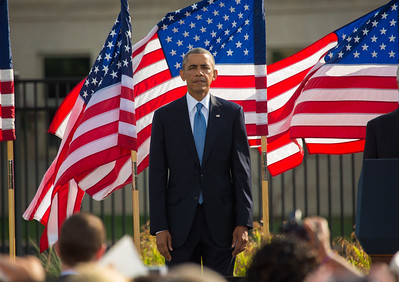 """At a solemn ceremony, President Barack Obama observed the 13th anniversary of the Sept. 11 attack on the Pentagon which claimed the lives of 184 individuals. The ceremony at the Pentagon was mostly private, attended by family members of victims of the attack, first responders and senior military and government officials. The public was allowed to view the memorial following the ceremony. Observances got underway in the D.C. area at dawn with the unfurling of an American flag down the side of the Pentagon. The tradition began Sept. 12, 2001, when firefighters unexpectedly got onto the building's roof and draped a large flag across the damaged building, a symbol of America's resolve. The commemoration service began at 9:30 a.m., hosted by Secretary of Defense Chuck Hagel and Chairman of the Joint Chiefs of Staff Martin Dempsey. President Obama spoke following the playing of TAPS and a moment of silence at 9:37 a.m., the moment an airliner hit the Pentagon. The President offered words of comfort to the families, telling them """"Your love is the ultimate rebuke to the hatred of those who attacked us."""""""