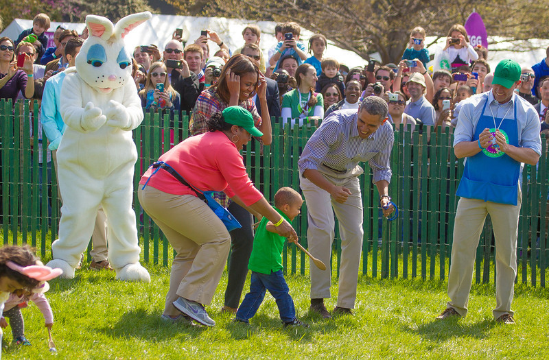 "Thousands of kids joined the First Family on a sunny Easter Monday for the 136th White House annual Easter Egg Roll. An estimated 30,000 were on hand to see President Barack Obama introduce his wife Michelle as ""the person who makes this all possible"". The theme of this year's egg roll was ""Hop into Healthy, Swing into Shape,"" part of the first lady's Let's Move initiative. The President once again read from ""Where the Wild Things Are"" and the First Lady greeted scores of children with hugs. The Obama kids, Sasha and Malia could not attend because they were in school, but the First Dogs, Bo and Sunny were on hand to greet the visitors"