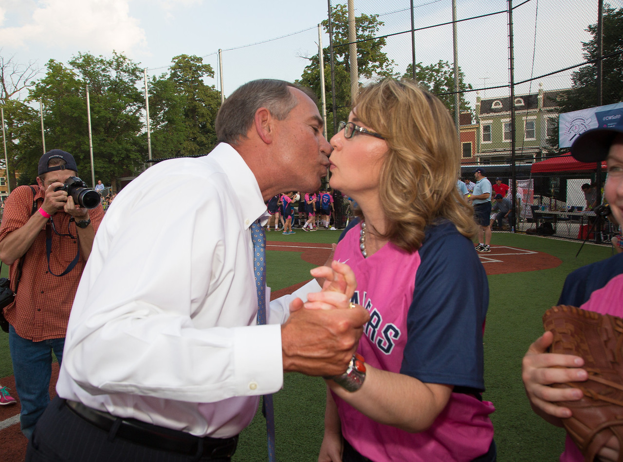 Speaker of the U.S. House of Representatives, John Boehner (R-Ohio), kisses former U.S. Congresswoman Gabrielle Giffords, who was on hand to throw out the ceremonial first pitch at the Sixth Annual Congressional Women's Softball Game in Washington D.C. on June 18, 2014. The game was won by the Congressional Members team over the Press team by a score of 10-5. The game raised $150,000 to combat breast cancer. Giffords had played in the inaugural Congressional Women's Softball Game in 2009. On Jan. 8, 2011, Giffords, the former House Democrat from Arizona was shot along with 18 others, six of whom died, at a constituent meeting in a supermarket parking lot in the Tucson metropolitan area. (Photo by Jeff Malet)