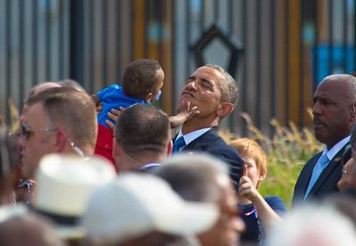 "Wearing a Superman outfit, 13 month old Larnell Maurice Perry Jr. is lifted in the air by U.S. President Barack Obama. Larnell's grandmother, Angelene C. Carter, died on September 11. She was an army accountant, only 51, from Maryland. At a solemn ceremony, President Barack Obama observed the 13th anniversary of the Sept. 11 attack on the Pentagon which claimed the lives of 184 individuals. The ceremony at the Pentagon was mostly private, attended by family members of victims of the attack, first responders and senior military and government officials. The public was allowed to view the memorial following the ceremony. Observances got underway in the D.C. area at dawn with the unfurling of an American flag down the side of the Pentagon. The tradition began Sept. 12, 2001, when firefighters unexpectedly got onto the building's roof and draped a large flag across the damaged building, a symbol of America's resolve. The commemoration service began at 9:30 a.m., hosted by Secretary of Defense Chuck Hagel and Chairman of the Joint Chiefs of Staff Martin Dempsey. President Obama spoke following the playing of TAPS and a moment of silence at 9:37 a.m., the moment an airliner hit the Pentagon. The President offered words of comfort to the families, telling them ""Your love is the ultimate rebuke to the hatred of those who attacked us."""