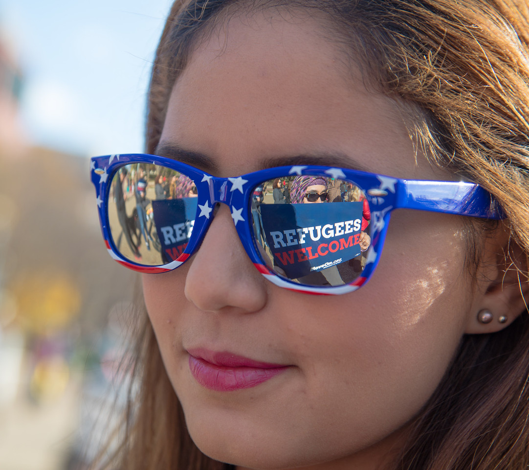 """""""Refugees Welcome"""" sign is reflected in the sunglasses of Jihane, a Georgetown University student. Chanting """"Let them in"""", hundreds of demonstrators rallied outside the White House in support of allowing Syrian refugees to enter the United States. The rally in Washington D.C. took place on Saturday, November 21, 2015. President Barack Obama has planned to allow 10,000 Syrian refugees to enter the United States. Earlier in the week, the U.S. House of Representatives had voted to make it harder for them to do so because of concerns that terrorists could pose as refugees and carry out attacks similar to those that recently took place in Paris. In addition, more than half of the country's governors have said they will no longer provide placement for the refugees."""