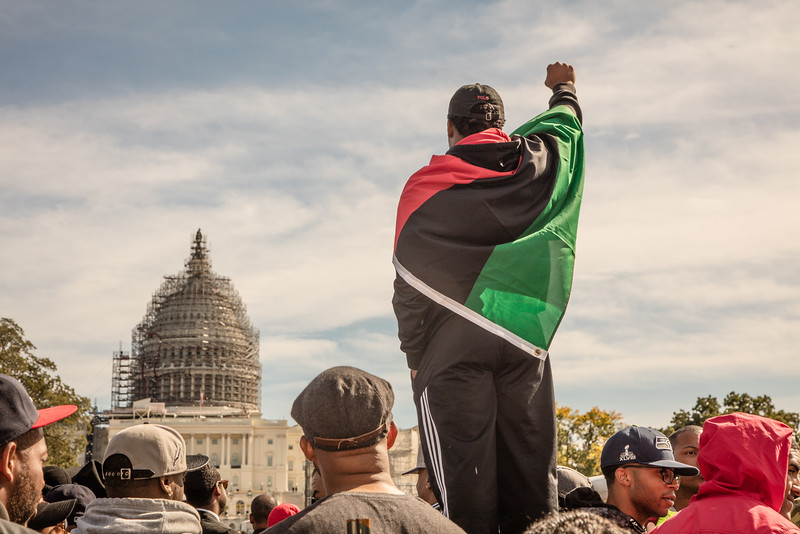 """Demonstrator points a fist in the direction of the Capitol while wrapped in the African American Heritage Flag. Thousands of black men and women from around the nation gathered to celebrate the 20th Anniversary of the Million Man March on the National Mall in Washington D.C. on Saturday October 10, 2015. Organized by Nation of Islam leader Louis Farrakhan, the theme of the rally was """"Justice or Else!"""", calling for policing reforms and changes in black communities."""