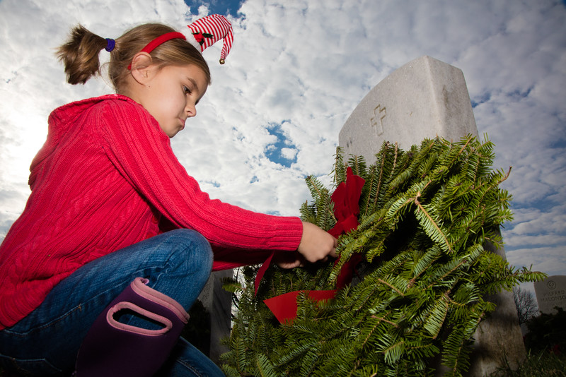 Eliza (age 5) of McLean Va. lays a wreath over the grave of Chief Master Sergeant Wilfred Malonson. Eliza was one of thousands who gathered at Arlington National Cemetery in Arlington Va. on Saturday, December 12, 2015 to lay holiday wreaths over each of the more than 240,000 graves. The 'Wreaths Across America' program, now in its 24th year, was started in 1992 by Morrill Worcester, owner of Worcester Wreath Company of Harrington, Maine with 5,000 wreaths. In total, over 901,000 remembrance wreaths were placed in over 1,100 locations nationwide on National Wreaths Across America Day.