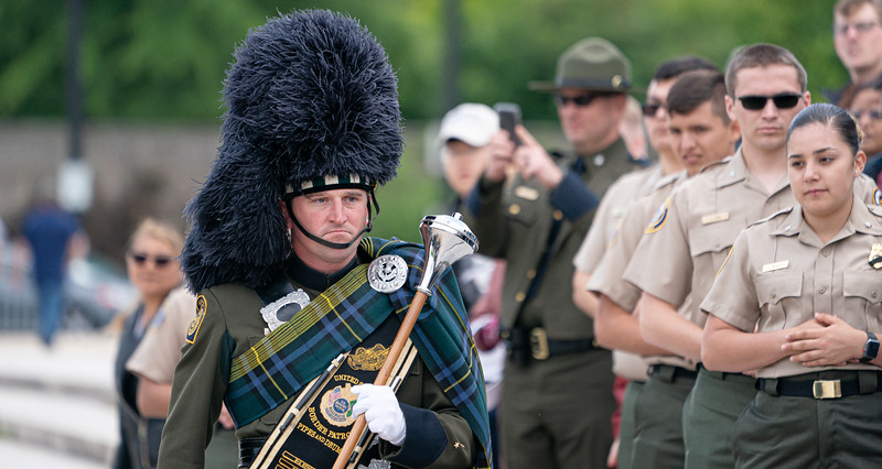 Drum Major Jeffery Swanson of the U.S. Border Patrol Pipes and Drums Band receives his first place trophy for his team during a competition at  Police Week. (photo by Jeff Malet)