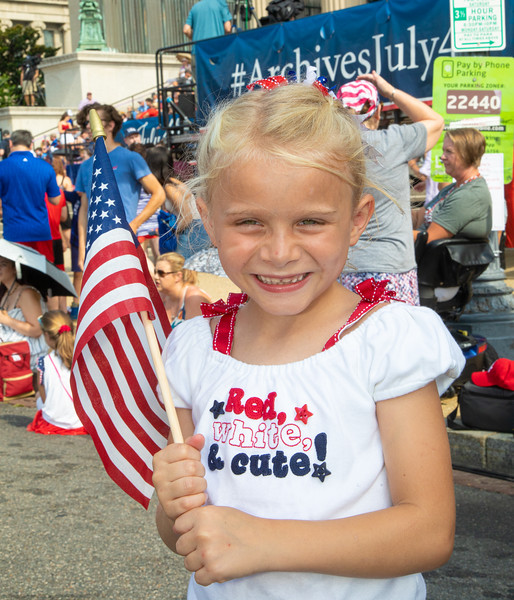 """Red, White and Cute."" Samantha, age 7, from Vienna, Virginia, enjoys the scene near the National Archives on Constitution Avenue. July 4, 2019. Photo by Jeff Malet."