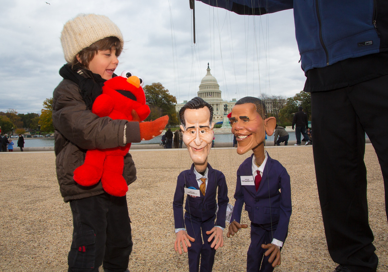 "Scott Land Marionettes from Los Angeles, CA and his Mitt Romney and Barack Obama Puppets participate in the ""Million Puppet March"" on the Capitol on Nov. 3, 2012 just three days before the presidential election. Four year old Apollo from Hyattsville MD watches with interest.  The march was a response to Mitt Romney's proposal during a presidential debate to reduce the national deficit in part by cutting funding for PBS and programs such as ""Sesame Street."""
