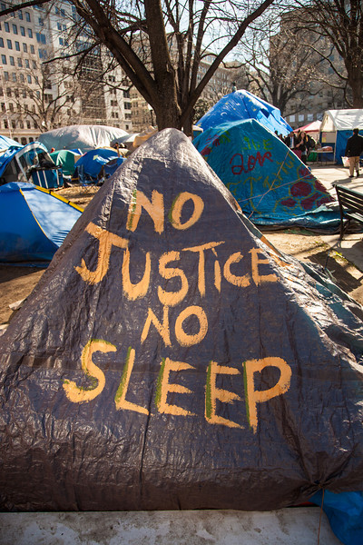 Under threat of expulsion, Occupy DC protestors defiantly drape the James McPherson statue with a blue tarp in McPherson Square in Washington DC on January 30, 2012.
