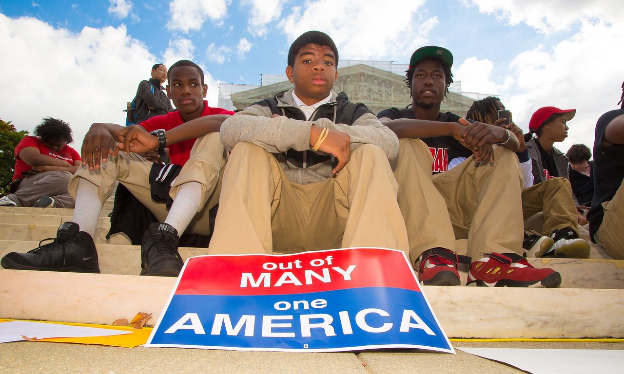 "LaDre Britt, a 14 year student from Dunbar High in Washington DC, sits on the steps in front of the U.S. Supreme Court  building on October 10, 2012. Britt's sign reads ""Out of Many, One America"". The Supreme Court was hearing a challenge to its long-standing ruling that race may be considered as a factor in the admissions process (affirmative action). Justices were debating the case of Fisher v. University of Texas. The outcome could have major implications for higher education. (Photo by Jeff Malet)"