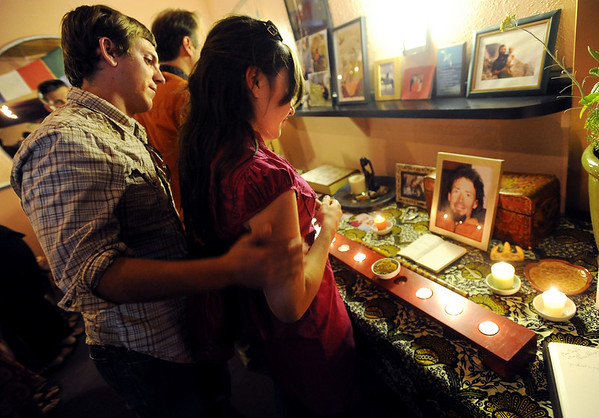 Matt Hicks, left, comforts Natalie Slevin, while the couple look at a photo of friend Jonny Copp.<br /> A memorial service celebrating the lives of Jonny Copp, Micah Dash, and Wade Johnson was held Saturday at the Boulder Theater. The three men died in an avalanche this spring while on a climbing expedition in western China's Sichuan province.<br /> <br /> Cliff Grassmick / July 11, 2009