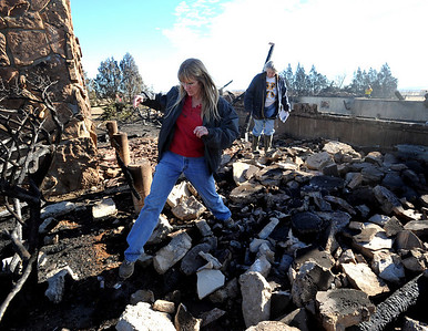 Lydney Nichol, left,  and Bobra Goldsmith walk through what is left of Goldsmith's home on Thursday. Llama Rancher, Bobra Goldsmith, lost her home to one of the wind generated fire, but no people or llamas were injured at the ranch at 7202 45th Street. Cliff Grassmick/ January 8, 2009