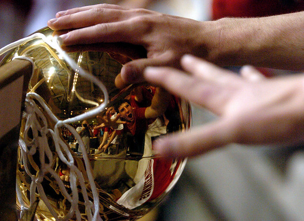 Regis Jesuit fans reach out to touch the 5A state championship trophy.<br /> Cliff Grassmick / March 14, 2009