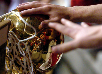 Regis Jesuit fans reach out to touch the 5A state championship trophy. Cliff Grassmick / March 14, 2009