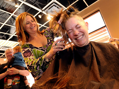 "Alex Teller grimaces as large chunks of her hair are taken off by Nancy Cassela. The non-profit group ""There With Care""  that helps critically ill children, hosted the ""Give Hair With Care"" event at Salon Salon in Boulder on Sunday. Dozens of people came in for a haircut and donated their hair to Wigs for Kids. Cliff Grassmick / March 8, 2009"
