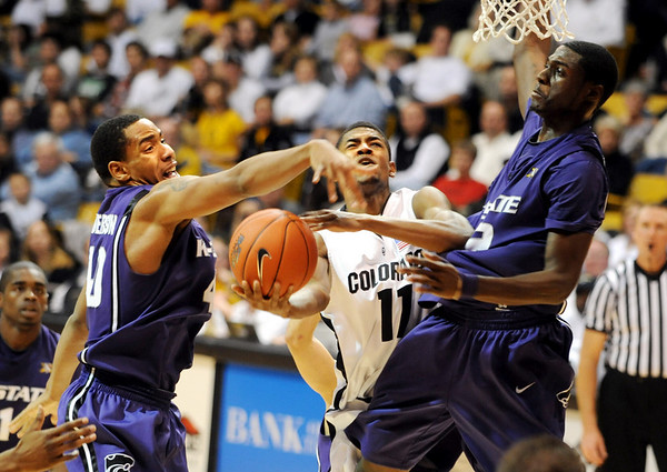 Cory Higgins draws the foul while driving between Ron Anderson and Luis Colon of KSU.<br /> Cliff Grassmick / January 24, 2009