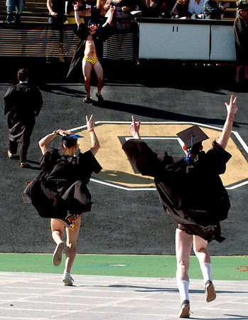 Robert Craig and Brian Robertson, both members of the CU water polo team, run up to greet teammate Josh Zeldner before graduation.<br /> About 5,280 degrees were conferred Friday  during the 2009 University of Colorado Spring Commencement at Folsom Field.<br /> Cliff Grassmick / May 8, 2009