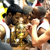 Erik Fielder, left, Kamryn Williams and Jamil Cooks kiss the 4A Colorado State Championship trophy after beatng Pueblo South on March 14, 2009 in Boulder.<br /> Cliff Grassmick / March 14, 2009