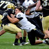 Michael Sipili loses his helmet while tackling Rodney Stewart during the CU Spring game on Saturday.<br /> Cliff Grassmick / April 25, 2009