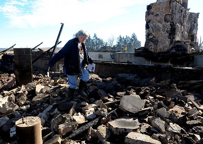 Bobra Goldsmith walks through the rubble that was her home on Thursday. Llama Rancher, Bobra Goldsmith, lost her home to one of the wind generated fire, but no people or llamas were injured at the ranch at 7202 45th Street. Cliff Grassmick/ January 8, 2009