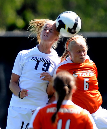 Lauren Shaner, left, of CU and Kasey Langdon of Oklahoma State hit the ball about the same time in a battle on Saturday.<br /> Cliff Grassmick / August 22, 2009