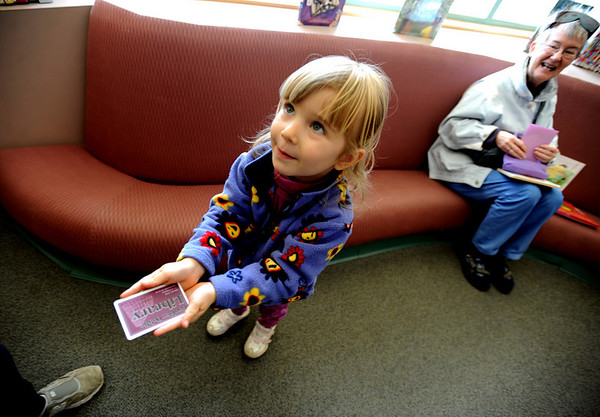 """Jady Laub, 3, shows her her mother her new library card she got at the Meadows Branch Library. Her grandmother Mary Ann Eckstein is in the background.<br /> The Meadows Branch of the Boulder Public Library system has been put on the chopping block of budget cuts. See more photos at  <a href=""""http://www.dailycamera.com"""">http://www.dailycamera.com</a>.<br /> Cliff Grassmick / March 6, 2009"""