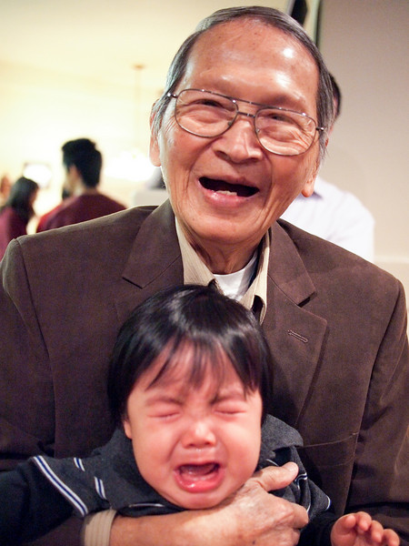 Grandpa holds baby Nathan, perhaps against his wishes, at the Phamily Christmas Party