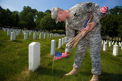 Staff Sergeant Richard Carnicom of Echo Company, 4th Battalion, 3rd U.S. Infantry Regiment, the Old Guard, places flags on the gravestones of service members buried at Arlington National Cemetery on May 26, 2011.